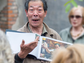 """Photo: Photoshop CC Before & After I may yet save some """"lost"""" photos.  Mr. Lee #2  This is Mr. Lee (or perhaps, Mr. Li), a retired international cricket wrangling champion. Here, he shows a group of onlookers his scrapbook of newspaper clippings and mementos. Later he regaled the group with some of his live crickets and grasshoppers. He is an enormously entertaining character.  The disappointment with the raw file I captured was that it was quite unsharp due to a bit of camera shake and probably, just missing the mark with lens focus. I have produced versions of this photo several times, coming to some reasonably acceptable compromises, since the expression on Mr. Lee's face is simply too precious to disregard the photo altogether.  The first of these pictures is the unprocessed, unfocused original. Number two is after running it through the new Photoshop CC shake reduction filter on two layers- the first for overall sharpening and a copy of that one to add a little extra sharpness to the eyes. The layers were masked for the final sharpened result, then merged into a single layer. The resulting layer was then masked and the foreground and background were blurred with the lens blur filter in order to make Mr. Lee the most focused thing in the picture. Finally, two levels layers were used- one to adjust the overall scene, and a second one to darken the surroundings, again making Mr. Lee the feature of the scene.  If you look at them in order, you'll see the transformation from a disappointing unfocused shot into something that I think brings out the fun personality of Mr. Lee and eiliminates distractions both in front of and behind him."""