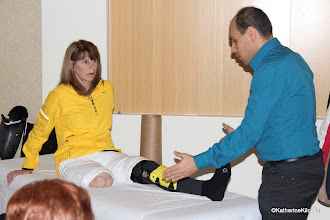 Photo: Carl, massage therapist with the 4mClub demonstrates how he creates balance between my phantom leg and my existing braced leg.  With improved balance I am more stable in the bath, standing, and even resting.  This was a huge gift.