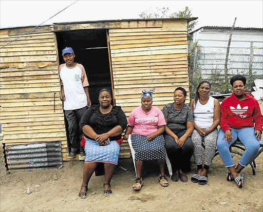 COMPASSION: Thuma-mna, an organisation in Nompumelelo, built a homeless man a wooden structure last week. Standing is the happy owner, Luyanda Sbharho, who previously lived on a dump. Seated from left are Zoliswa Tsonono, Simamkele Nongongo, Esethu Busakhwe, Bukelwa Sigonyela and Thulisiwe Solomon Picture: MICHAEL PINYANA