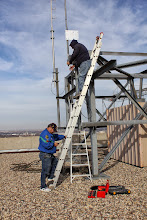 Photo: Glen holds the ladder for safety while Garth secures the antenna mast