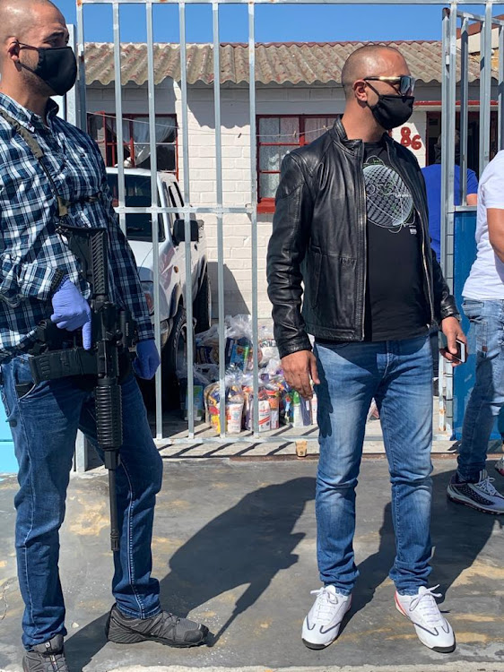Alleged underworld figure Nafiz Modack and his bodyguard at a house in Eldorado Park where he handed out food this week.