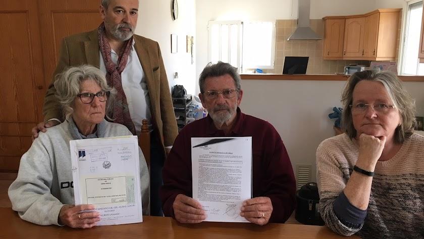 Los Payne sentados a la izquierda, mostrando la licencia de obras y la escritura.