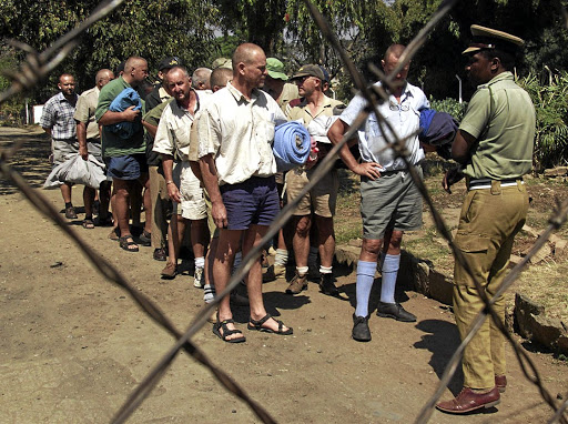 Zimbabwean farmers from Chinoyi line up for release at the town prison in 2001. The 21 farmers and businessmen were arrested after clashes with war veterans and Zanu-PF supporters and were jailed for 16 days on charges of inciting public violence.