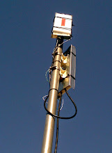 Photo: Closeup of a Ubiquiti Nanostation M5 and Nanostation M2 Loco hung on the same mast, with improvised shielding.