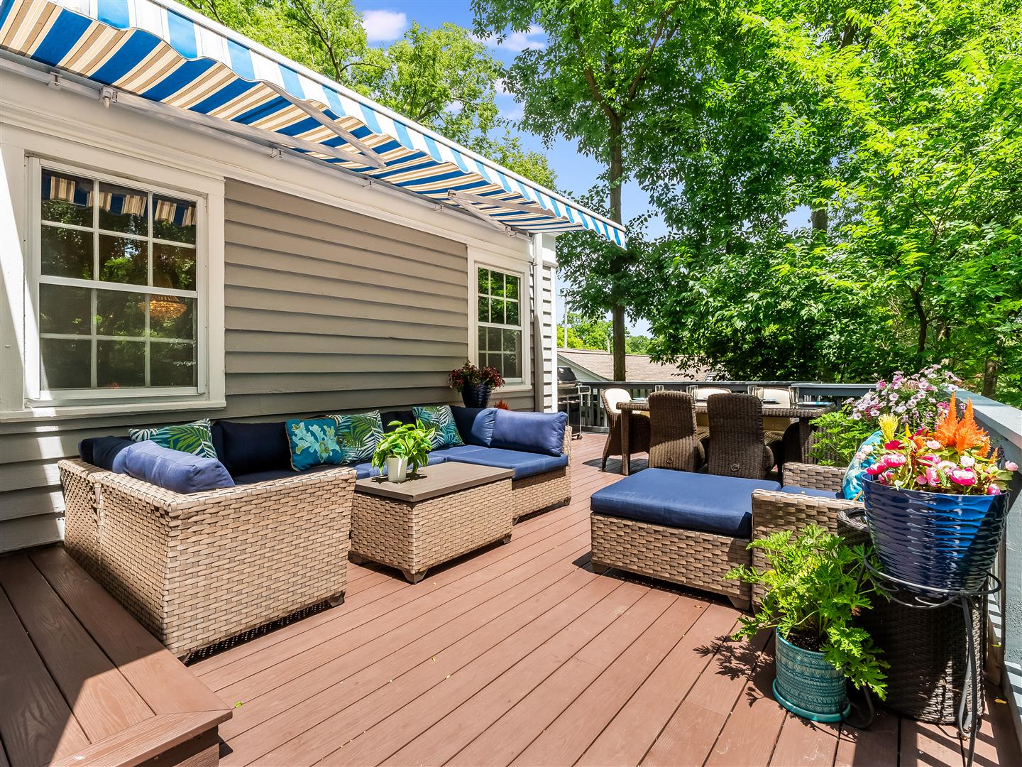 Outdoor deck with retractable awning, a dining space and conversational section surrounded by lush green trees.