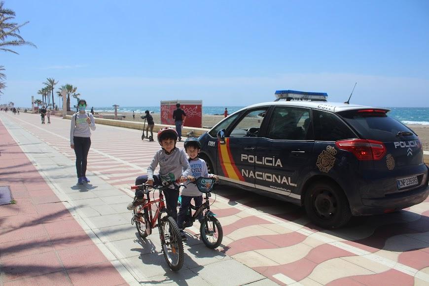 Con las bicicletas y junto a su madre, ante el coche patrulla de la Policía Nacional.