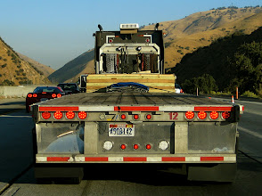"""Photo: Flat-bed truck.  I-5, LA to San Francisco.  A brief traffic jam allowed me to get the car almost exactly """"on axis""""."""