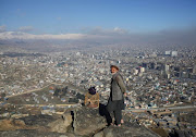 An Afghan man stands beside a bird cage on a hilltop overlooking Kabul, Afghanistan February 27, 2018.