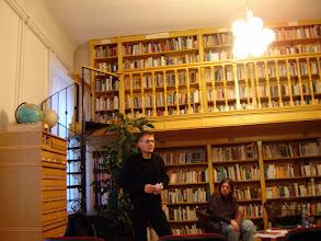 Photo: Balról Nedelkovics László, könyvtáros-rendezvényszervező megnyitja az irodalmi estet; jobbról az ülő alak Rusz Sándor költő, az est egyik házigazdája.