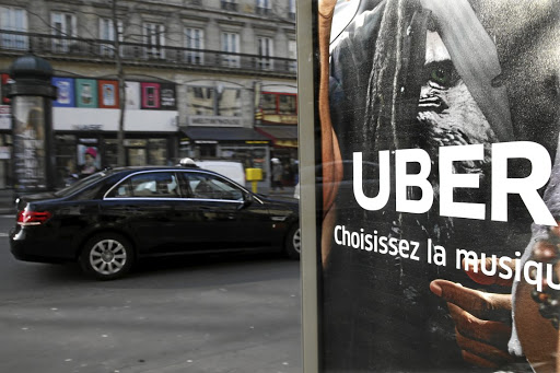 A taxi passes by an advertisement for the Uber car and ride-sharing service displayed on a bus stop in Paris, France. Picture: REUTERS