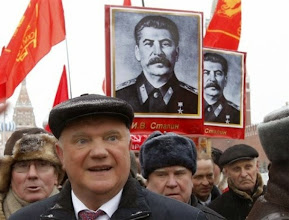 Photo: Russian Communists leader Gennady Zyuganov, 2nd left, smiles as others hold portraits of Soviet dictator Josef Stalin after laying flowers at his grave to mark the 130th anniversary of Stalin's birth Red Square in Moscow, Russia, Monday, Dec. 21, 2009. (AP Photo/Alexander Zemlianichenko)