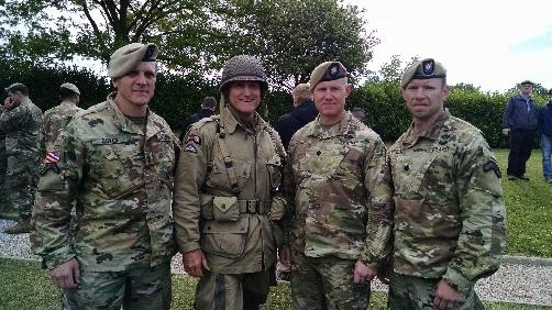 A group of people standing in front of a military uniform  Description automatically generated