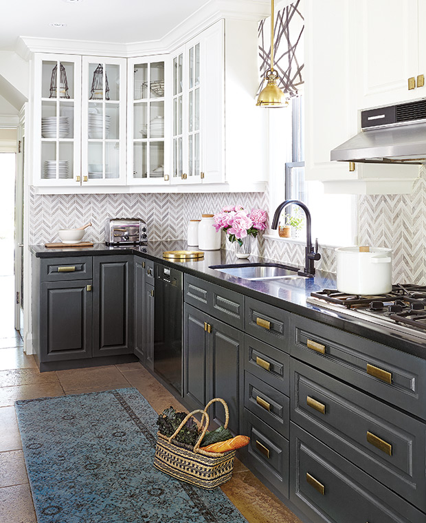 eclectic two toned kitchen with navy and white cabinets, gold hardware, black countertops and patterned blue rug