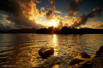"""Photo: Staring At The Sun  As I stand and let you bathe me in light The world turns to gold And the heavens open To the sound of ripples on the shore I'm staring at the sun And I'm no longer blind.  I take multiple shots sometimes of the same image but not always the same way, this is without the log exposure I used here at the same spot on an image called """"Fly From The Sun"""" : https://lh3.googleusercontent.com/-QBBaxUWjfq4/Tpxp5xc7ODI/AAAAAAAAOMM/G2B9RZKGWMg/s900/Escape-II.jpg Once again this is Derwent Water in the Lake district, the place I always long to be when I am away.  My last image of the day, I'm struggling on G+ with the notification issue but hopefully it will be resolved soon :)"""