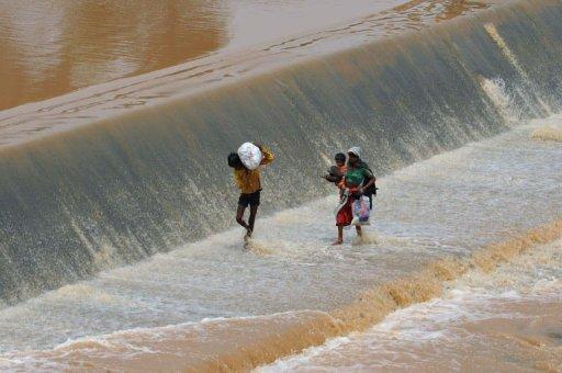 Photo: Des villageois indiens traversent un barrage à Pampa Sarovar, dans le district de Dang, à quelques 375 kilomètres d'Ahmedabad. (© 2012 AFP)