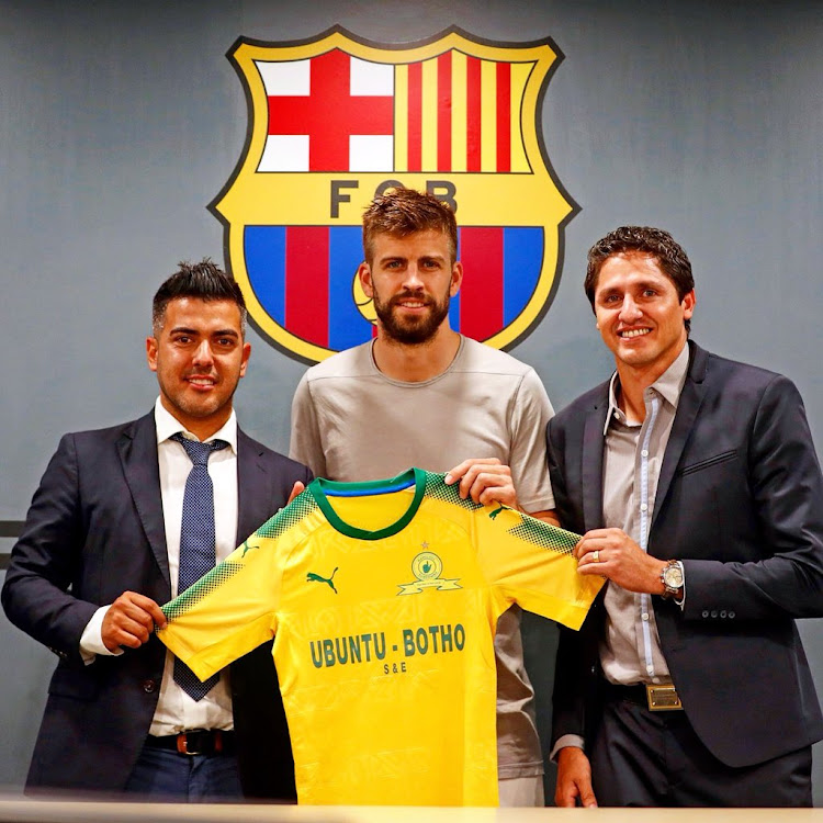 Gerard Pique (centre) holding a Mamelodi Sundowns football jersey.