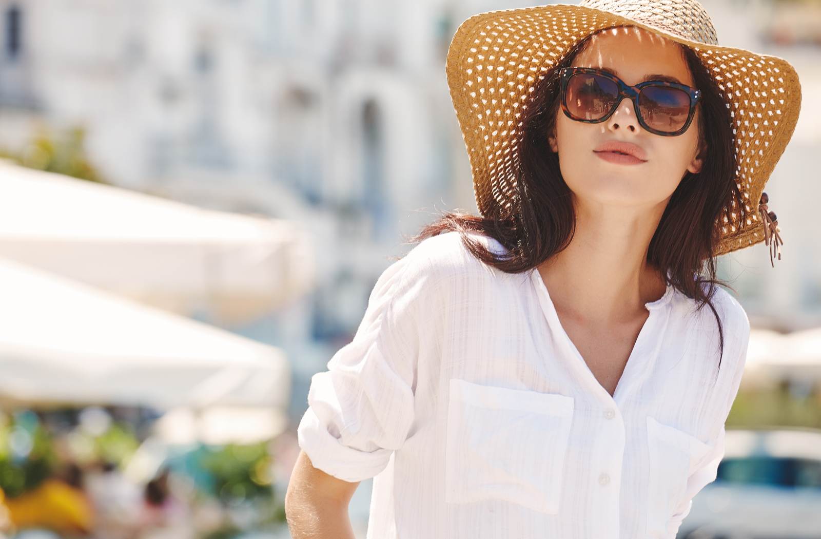 a dark haired woman wearing a floppy wide brimmed hat and sunglasses staring intently at something above the camera
