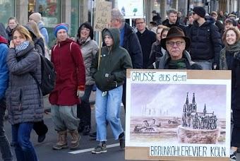 Demonstrant:innen, einer trägt Plakat «Grüße aus dem Braunkohlerevier Köln», es steht nur noch der Dom, ringsumher ist alles weggebaggert, im Hintergrund qualmende Schlote.