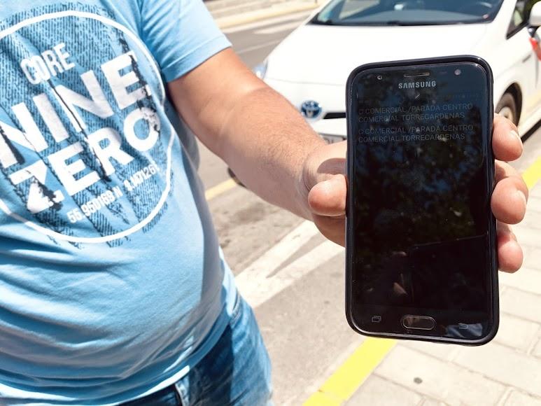 Un taxista muestra como le notifican de dos carreras en el CC Torrecárdenas, justo cuando lo abandonó debido a las altas temperaturas.