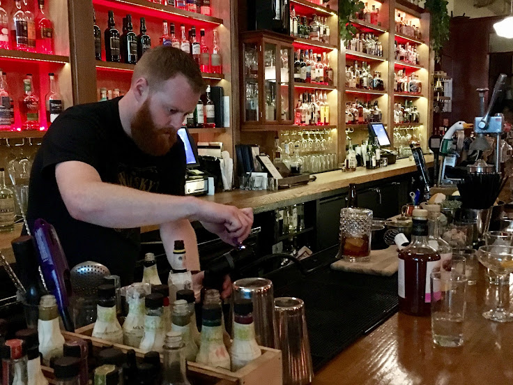 The bartender prepares a smoking gun to infuse a cocktail with hickory smoke.