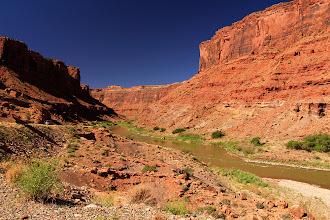 Photo: Le fleuve Colorado longe la route 128. De l'autre côté, les falaises rouges du parc Arches.