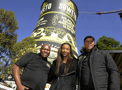 Soweto Gold founder and brew-master Ndumiso Madlala poses with Soweto artist Karabo Poppy Moletsane and former soccer ace Doctor Khumalo next to the Orlando cooling towers, now spotting Soweto Gold colours. / Veli Nhlapo