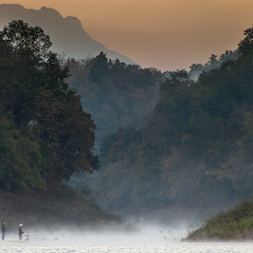 Fisherman rowing a boat through misty river by Natapong Paopijit - Landscapes Forests ( water, calm, lake, forest, boat, morning, landscape, rowboat, dusk, tranquil, foggy, dawn, nature, fog, scene, sunrise, fishing, fisherman, pond, misty, mist, river )