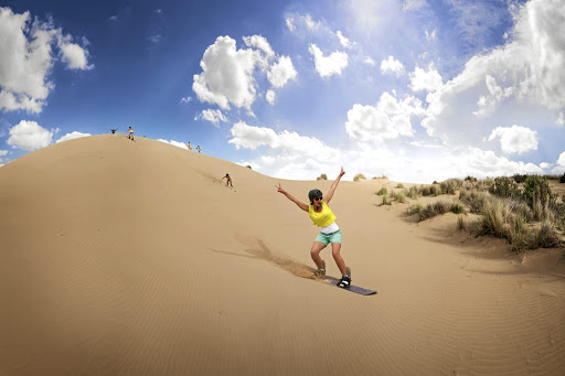 Plant your feet, or plant your face, sandboarding down the Alexandria Dunes, just outside PE.