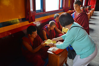 Photo: Shirley Fu as well as other YYEF traveling companions joined Jetsun Ma in the gift giving act at the Dialectic School of Menri Monastery.