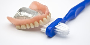 dentures lying next to a toothbrush