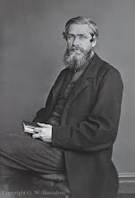 """Photo: Alfred Russel Wallace in c. 1869. In """"My Life"""" Alfred Russel Wallace says that this photo was taken in 1869 i.e. when he was aged 46 and living in Regent's Park, London. However, his son William thought it was taken between 1863 and 1866 (see http://wallacefund.info/national-portrait-gallery-portraits). A large version of this photograph, which has been painted over in oil paints, is in the National Portrait Gallery (the background must have been painted in since the original lacks the objects shown in the painting). A painting by Evstafieff of ARW in the Malay Archipelago was based on this image. Photographer: Thomas Sims. First published in ARW's My Life (1905). Photographed with permission from an original positive photograph on an 21.2 x 16.4 cm glass plate owned by the Wallace family. Copyright of photo: G. W. Beccaloni."""