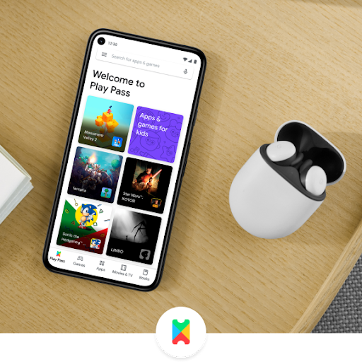 A phone rests on desk next to Pixel Buds. The phone shows the Google Play Pass interface.