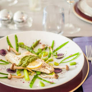 Oven-Baked Branzino with Blanched Spring Vegetables, Gourmet Mushrooms & Mint-Basil Pesto.