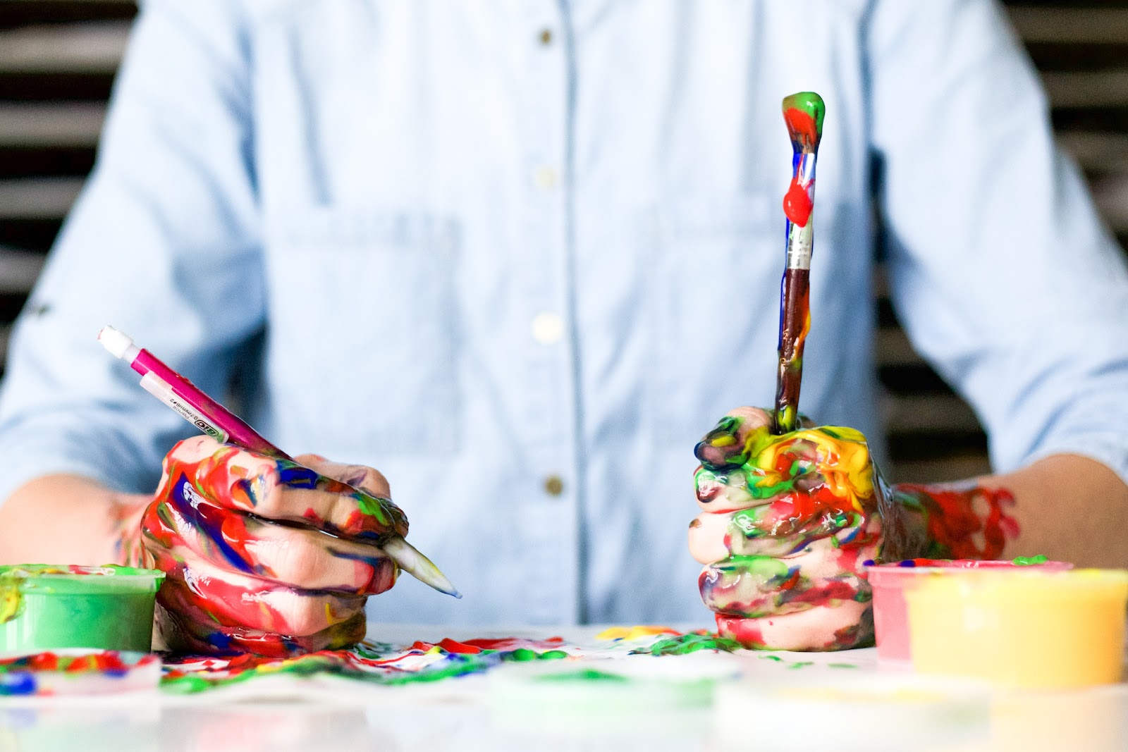 image of a person holding a paint brush and a pencil with multi-coloured paint spread around