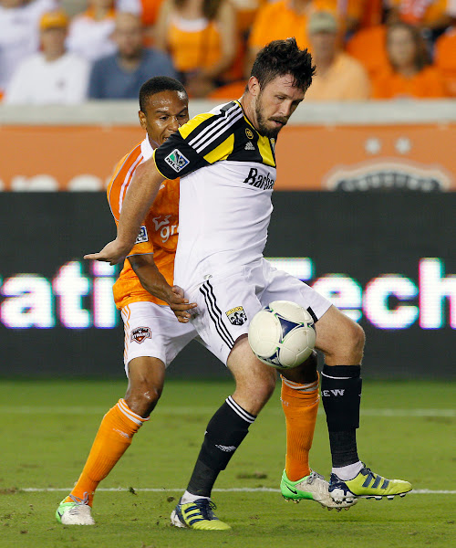 Photo: HOUSTON, TX - AUGUST 19:  Chris Birchall #8 of the Columbus Crew keeps the ball away from Ricardo Clark #13 of the Houston Dynamo in the second half at BBVA Compass Stadium on August 19, 2012 in Houston, Texas.  (Photo by Bob Levey/Getty Images)
