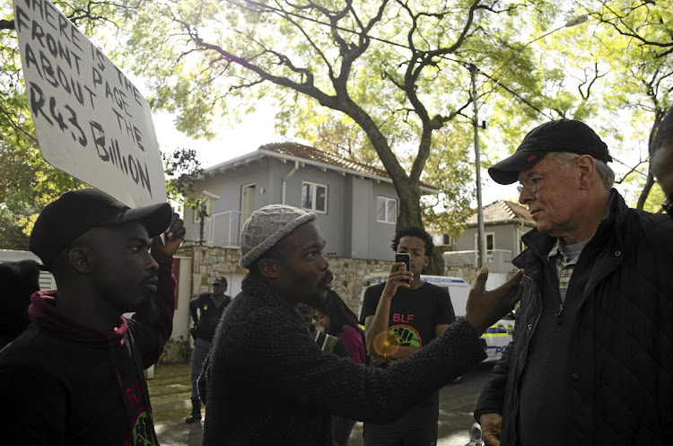 A  Black First Land First  member confronts former Business Day and Financial Mail editor  Peter Bruce outside his Johannesburg home yesterday over opinion pieces he wrote about the Gupta family.