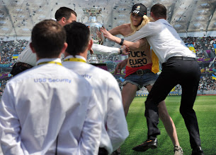 Photo: Security tries to stop an activist of Ukrainian women's movement FEMEN as she grabbed an EURO 2012 tournament cup during its display on Independence square in Kiev on May 12, 2012. Along with tournament co-hosts Poland and Ukraine, European football's governing body UEFA has organised a five-week trophy tour in cities across the two countries. AFP PHOTO / SERGEI SUPINSKYSERGEI SUPINSKY/AFP/GettyImages