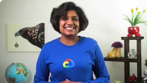 Mulher sorrindo com uma camisa azul do Google Cloud. Ao fundo, é possível ver um globo, uma pintura de uma ave e uma planta.