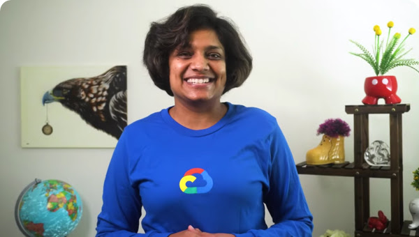 Woman in blue Google Cloud shirt smiling. In the background is a globe, a painting of a bird, and a plant.