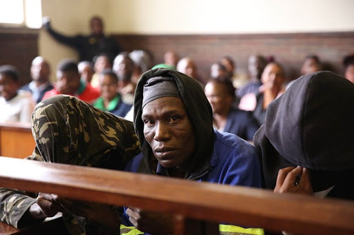 Seven men accused of eating human flash and who are facing charges of murder and attempted murder cower away from cameras while appearing in the Estcourt Magistrate Court on Thursday. Picture: THULI DLAMINI