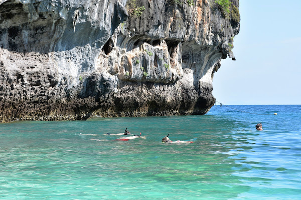 Snorkel in crystal clear water surrounded by vertical cliffs