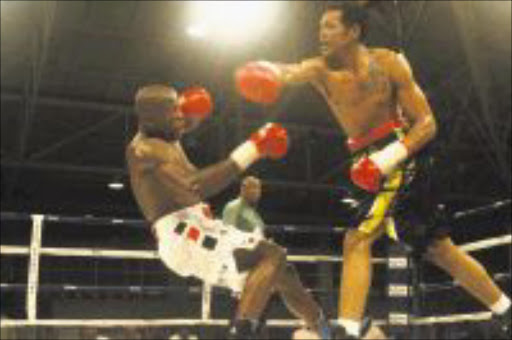 TAKE THAT! Tshepang Mohale, right, floors Khotso Motau during their national super middleweight title fight in Bloemfontein on Friday. Mohale won on points. Pic. BAFANA MAHLANGU. 09/08/2009. © Sowetan. 20090809 SA Super Middle Weight tiltle bout between Tshepang Mohale (black/yellow) outpointed Kgotso Motau (white/red) during their encounter in Bloemffontein on 07. 08.2009. Motau receiving one of the three knockdown. PHOTO: BAFANA MAHLANGU