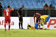 Sundowns' Thapelo Morena  is sprawled out  while his colleague,   Motjeka Madisha, and  Onismor Bhasera of SuperSport United, look on in Saturday's cup fixture.