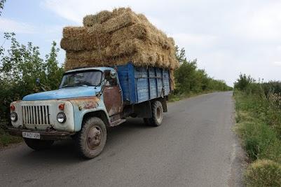 Ein alter Kamaz-LKW, vollbeladen mit Strohballen.