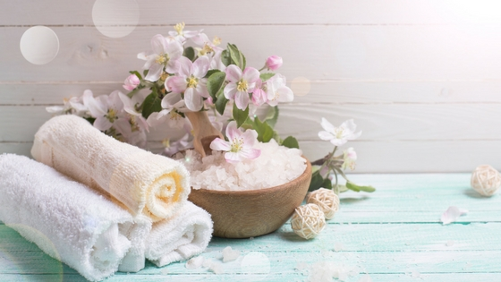 three towels rolled up and sitting next to a bowl of bath salts with lilies on top