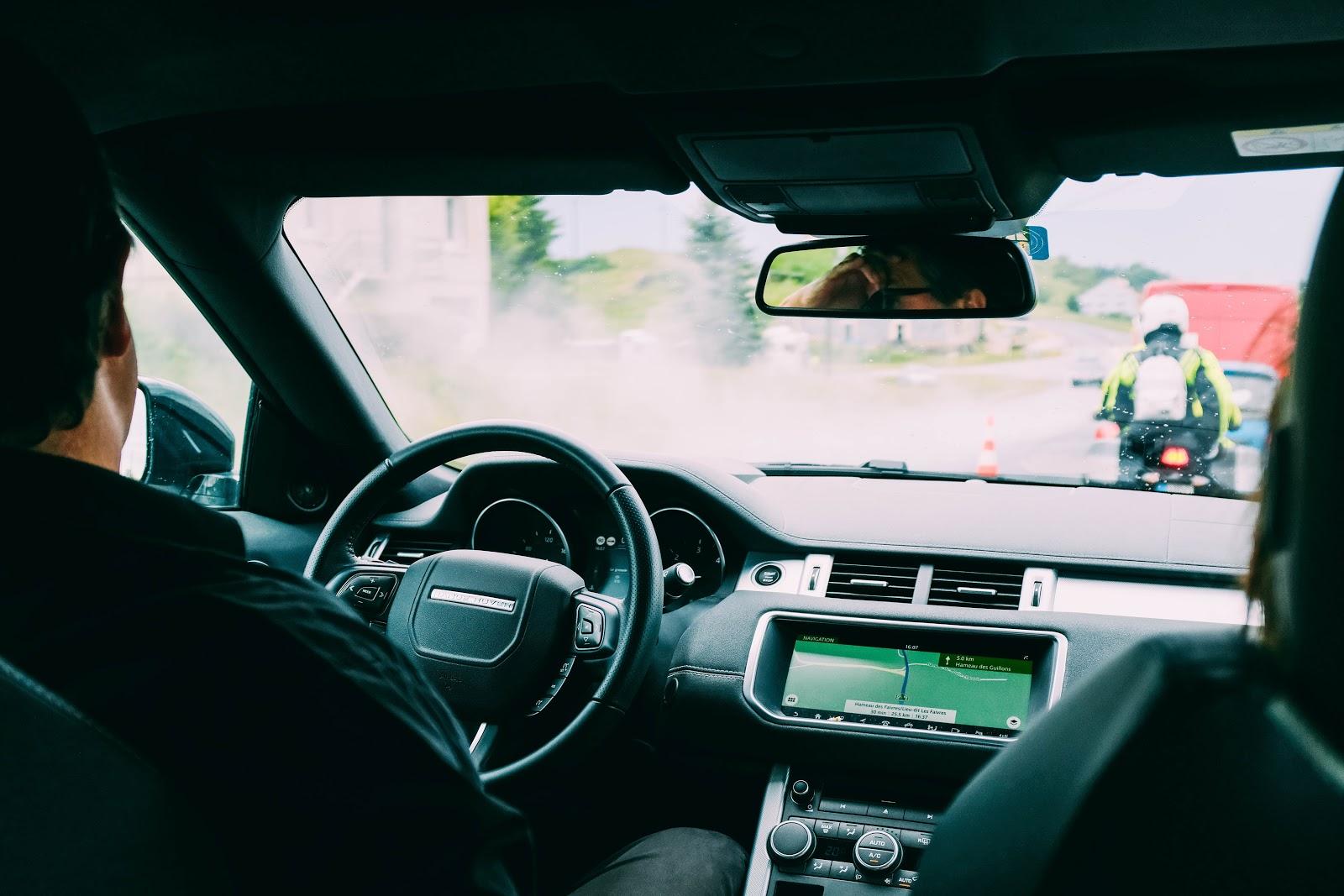 Motorista com passageiro ao lado dirigindo carro em carro.