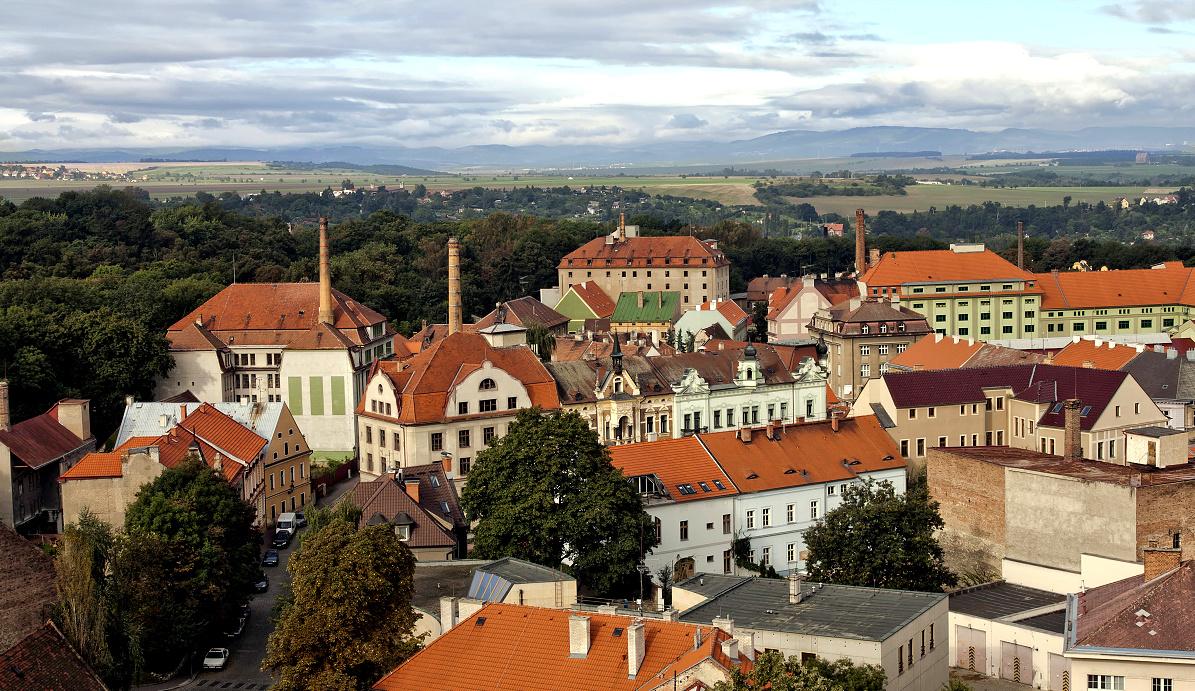 ikonický pohled na chmelařské sklady a panorama Krušných hor