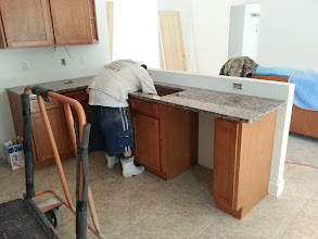 Photo: December 19, 2012 Hard at work on the granite. Killer boots, eh? The open wall above the sink will get a bar top slash counter later. Notice the leather sofa, covered – mostly – with spare mover's blankets (thanks, North American!). It'll be there for a while.