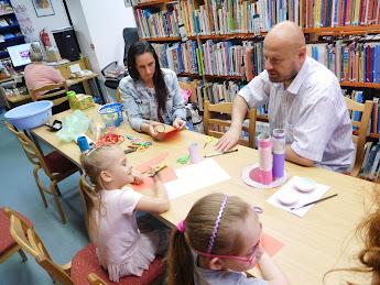 Papírt hajtogató család a könyvtárban