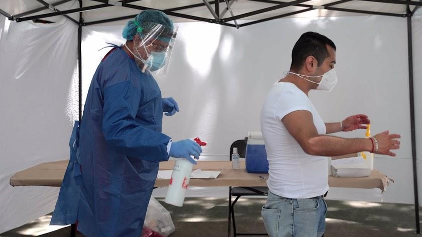 Sanitarios desinfectan a un paciente que va a someterse a una PCR.